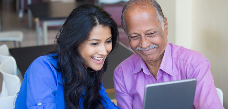 caregiver and elderly man using laptop