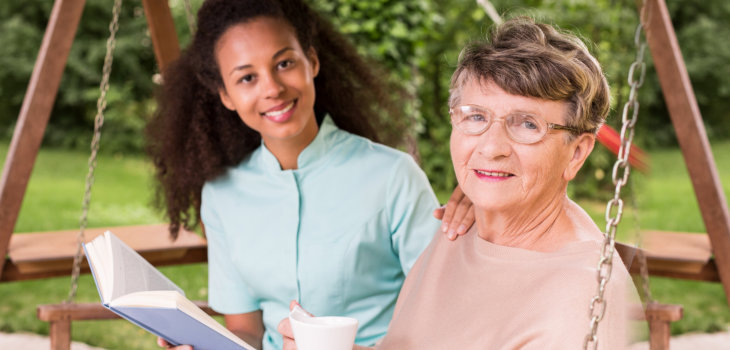 caregiver reading a book with the elderly woman